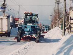 グレーダーで道路を除雪している風景
