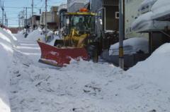 ショベルで道路の雪を押している風景