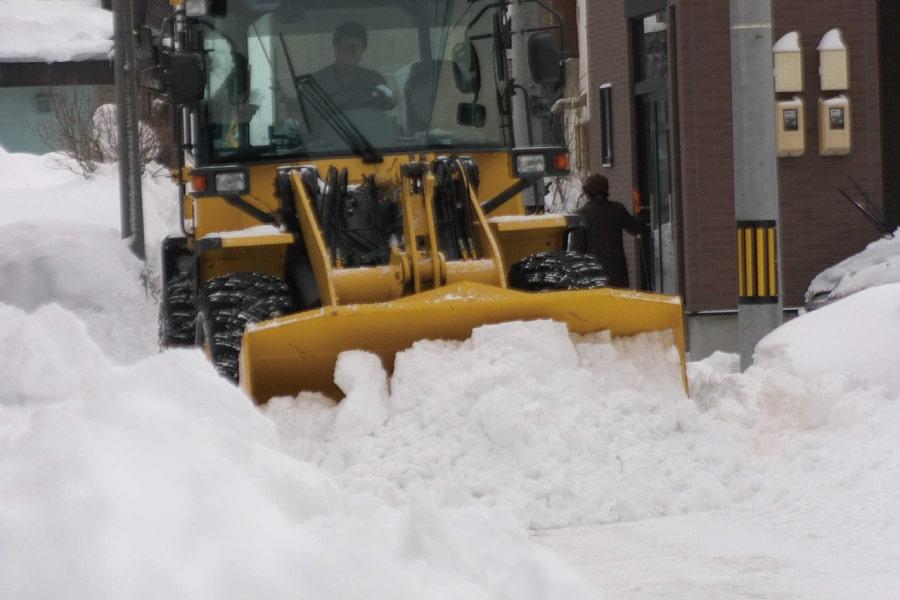 タイヤショベルで道路の除雪作業している様子