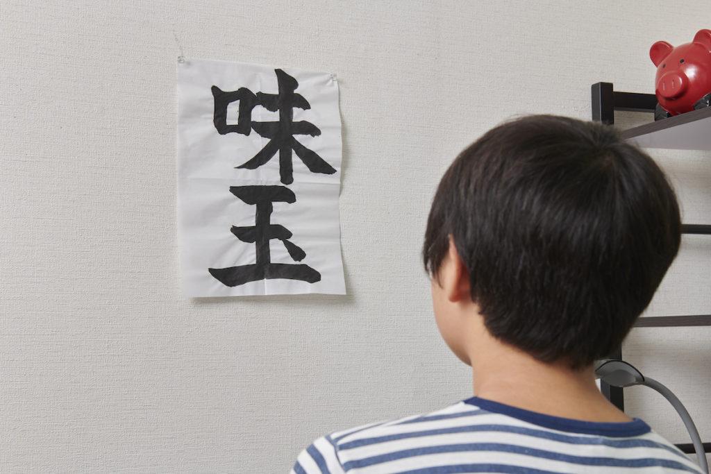 壁に張った習字を見る人