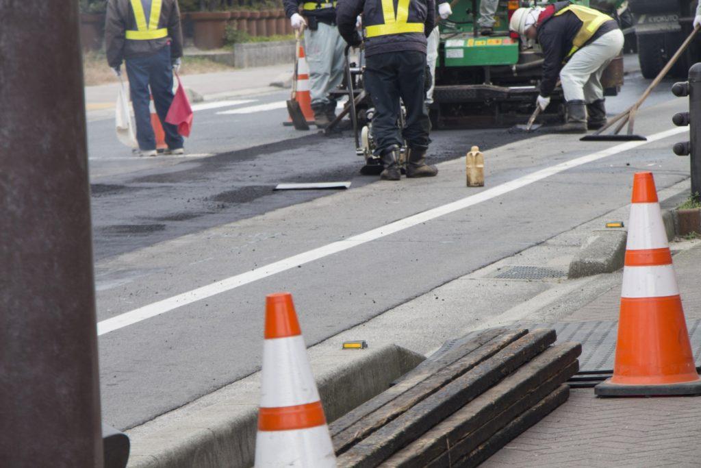アスファルトフィニッシャーで道路を舗装している様子