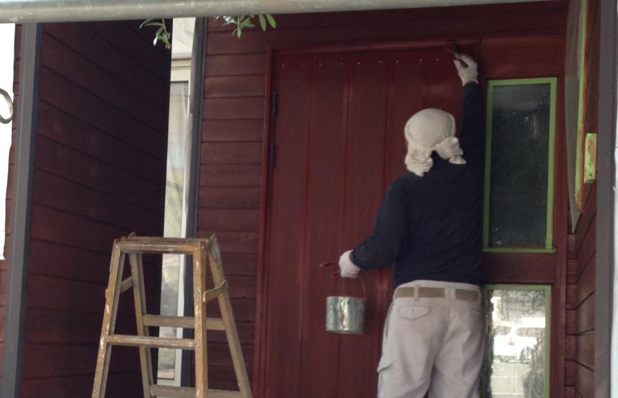 玄関を塗装する職人