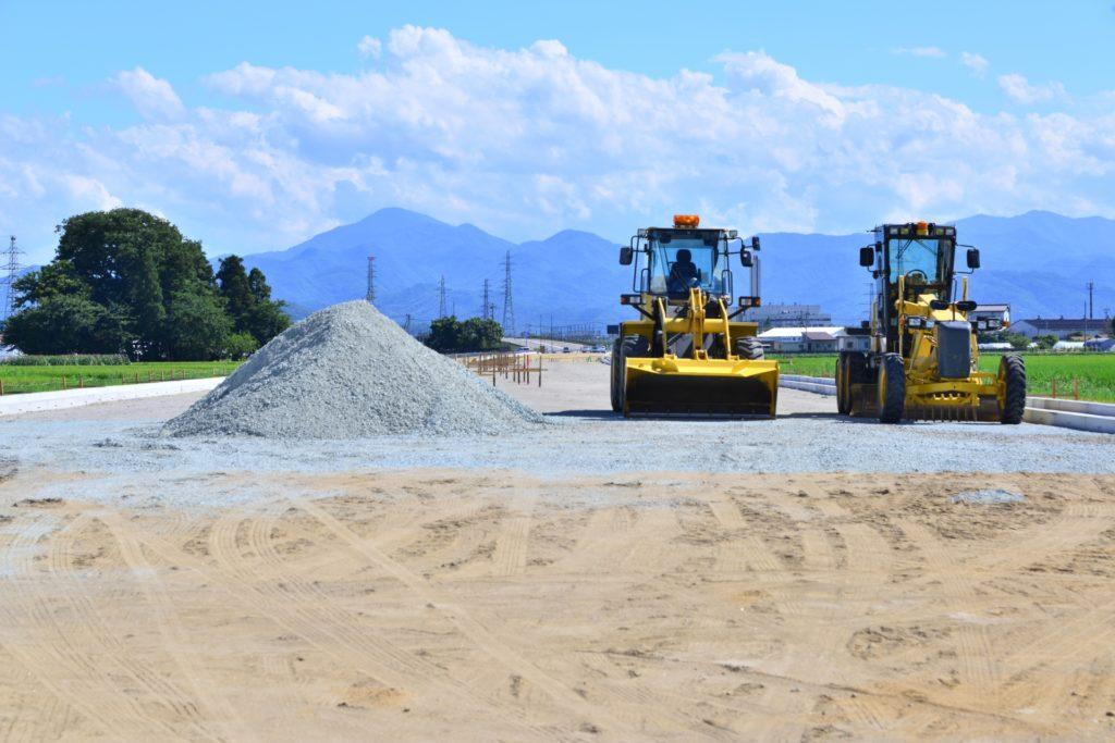 道路工事、ショベルとグレーダーの作業風景