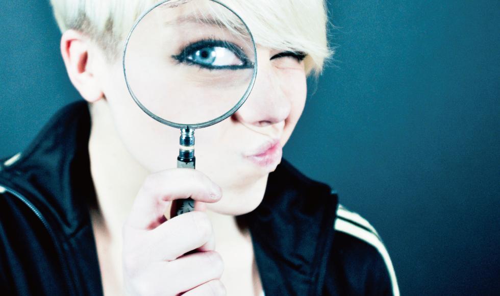 虫眼鏡をのぞき込む金髪の女性