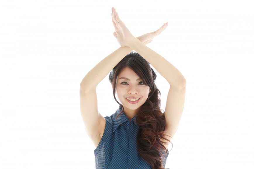 両腕でバツを掲げる女性
