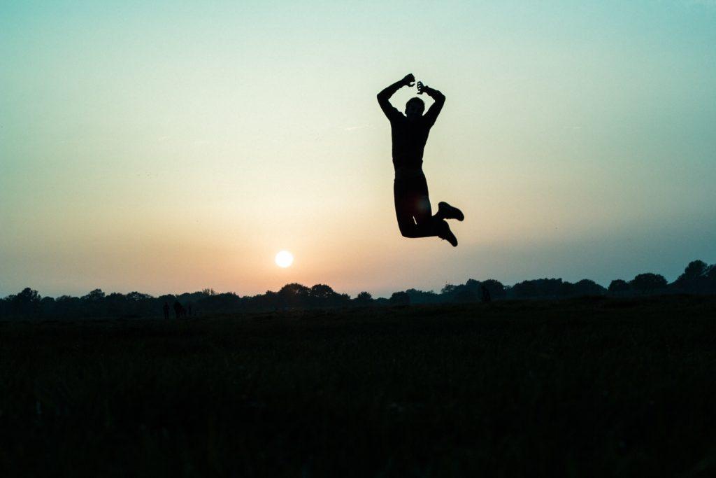 大自然で夕日をバックにジャンプする人