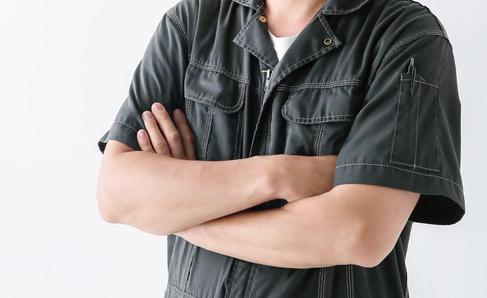 腕を組むつなぎを着た職人