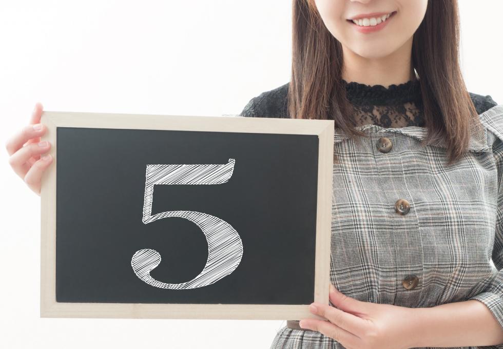 5を書いた黒板を持つ女性