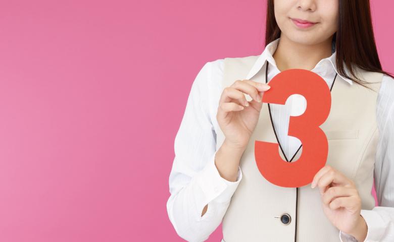 数字の3を掲げる事務の女性
