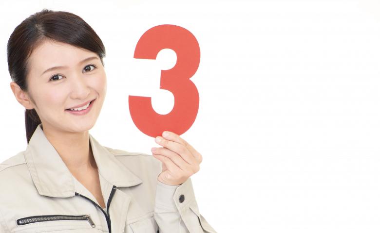 数字の3を持つ作業服の女性