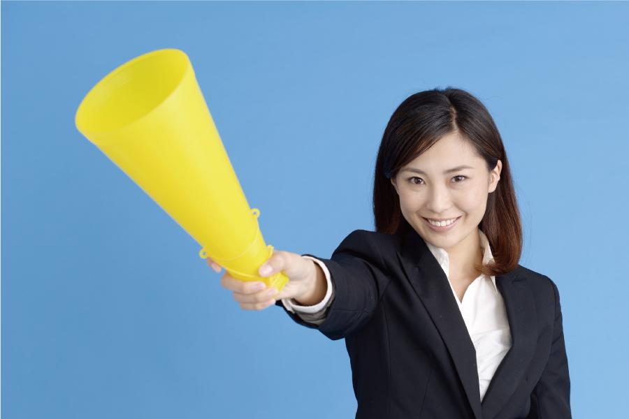 黄色いメガホンを持つスーツ姿の女性