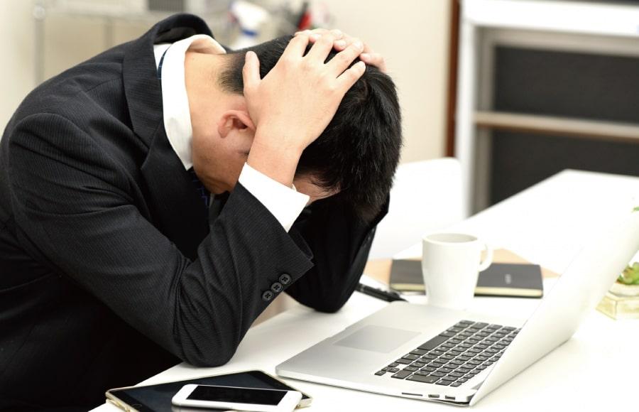 パソコンの前で頭を抱えるビジネスマン