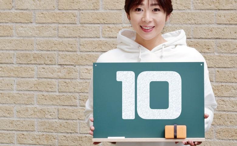 「10」と書いた黒板を持つ女性