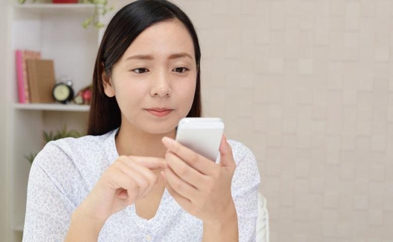 スマホでホームページを閲覧する若い女性