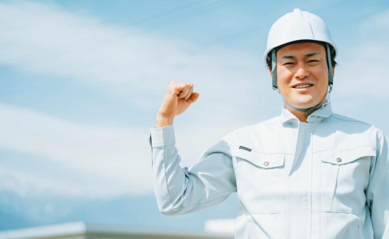 作業服にヘルメット姿の塗装屋の社長(イメージ)