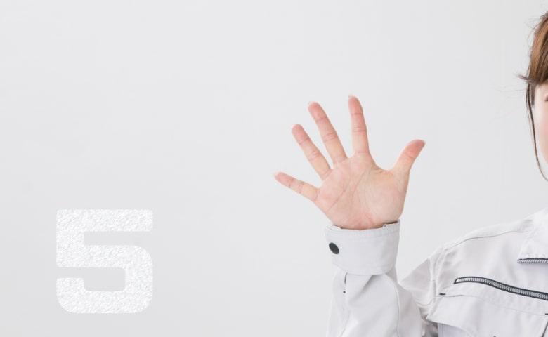 手で5を示す作業服の女性