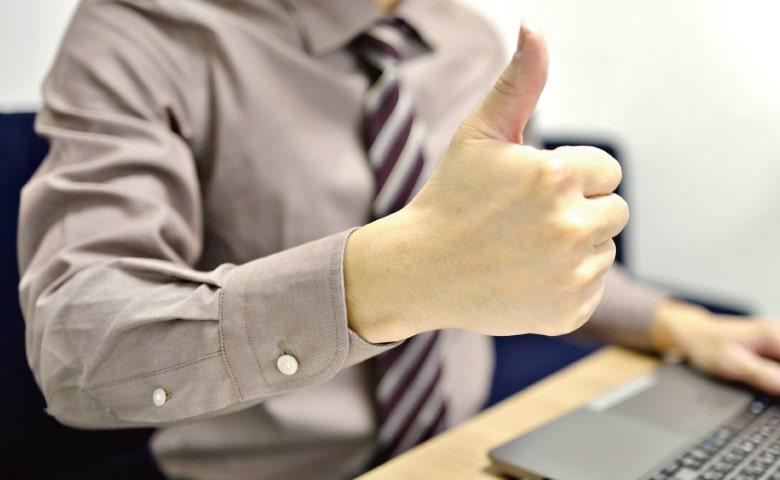 ノートパソコンの前でグッドのポーズをするスーツの男性