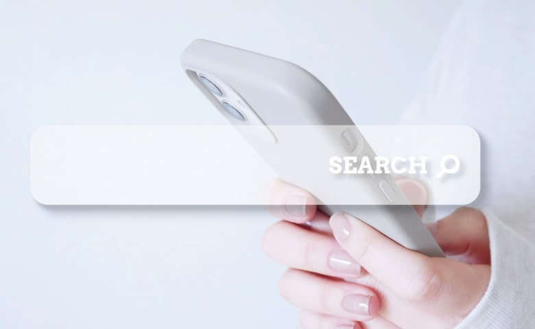 スマホを操作する女性の手と、検索窓(イメージ)