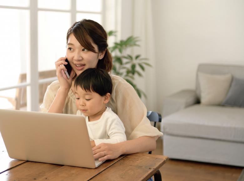 PCの前で子供を抱えながらスマホで電話するお母さん